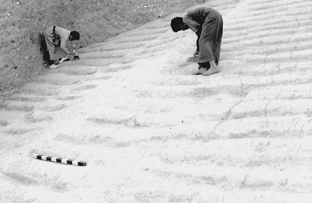 Two people in long robes bent over working on the White Monument