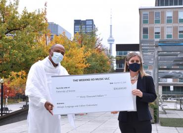 Bikila Award president Tessema Mulugeta presents Arts & Science Dean Melanie Woodin with The Weeknd's cheque for $30,000 – pushing the Ge'ez course's endowment past the $500,000 goal (photo by Diana Tyszko)